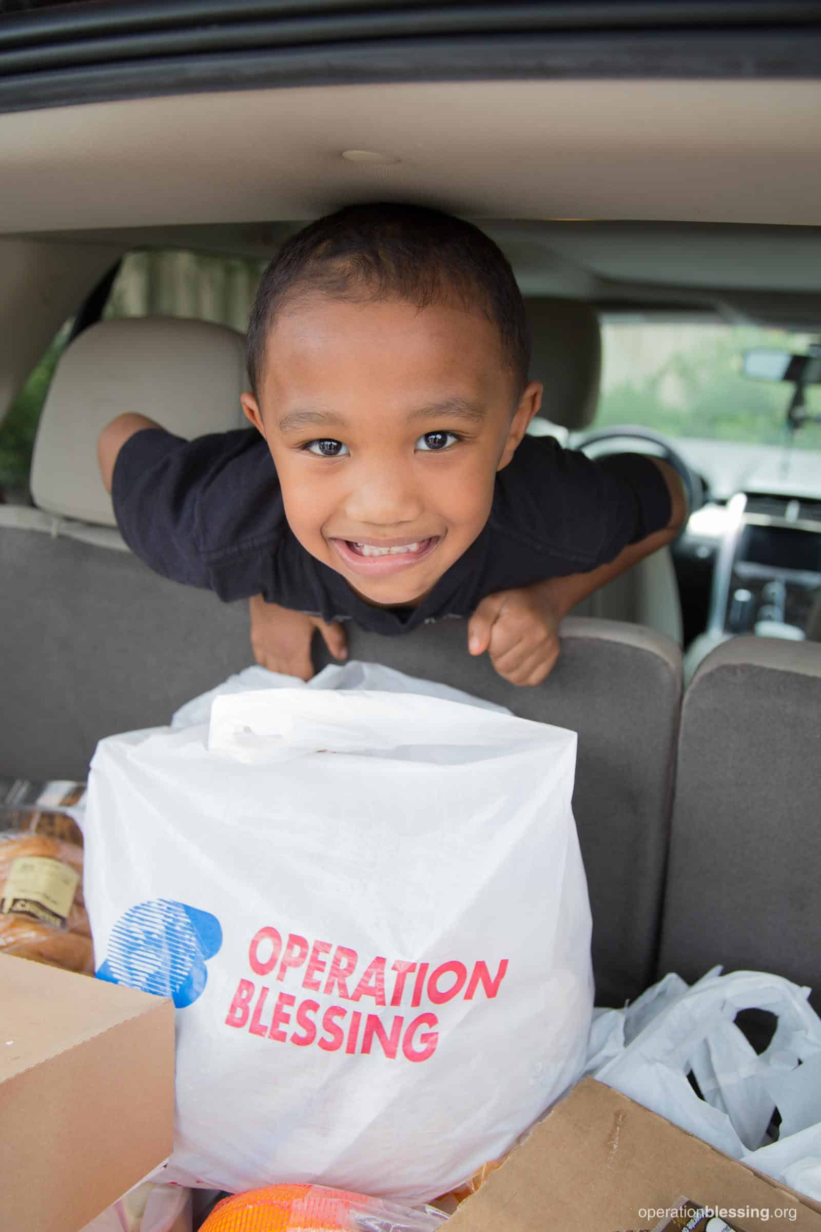Mayflor's son is excited as he peeks over the backseat of the car to see the groceries provided by Operation Blessing.