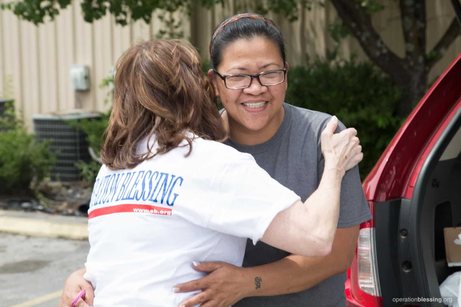 Mayflor receives an encouraging hug from an Operation Blessing worker.