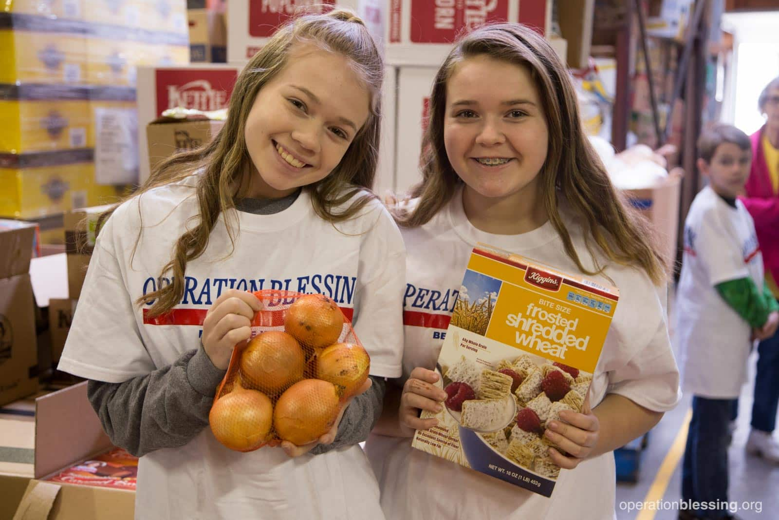 Two girls hold food provided by OBI's hunger strike force to feed Americans in need.