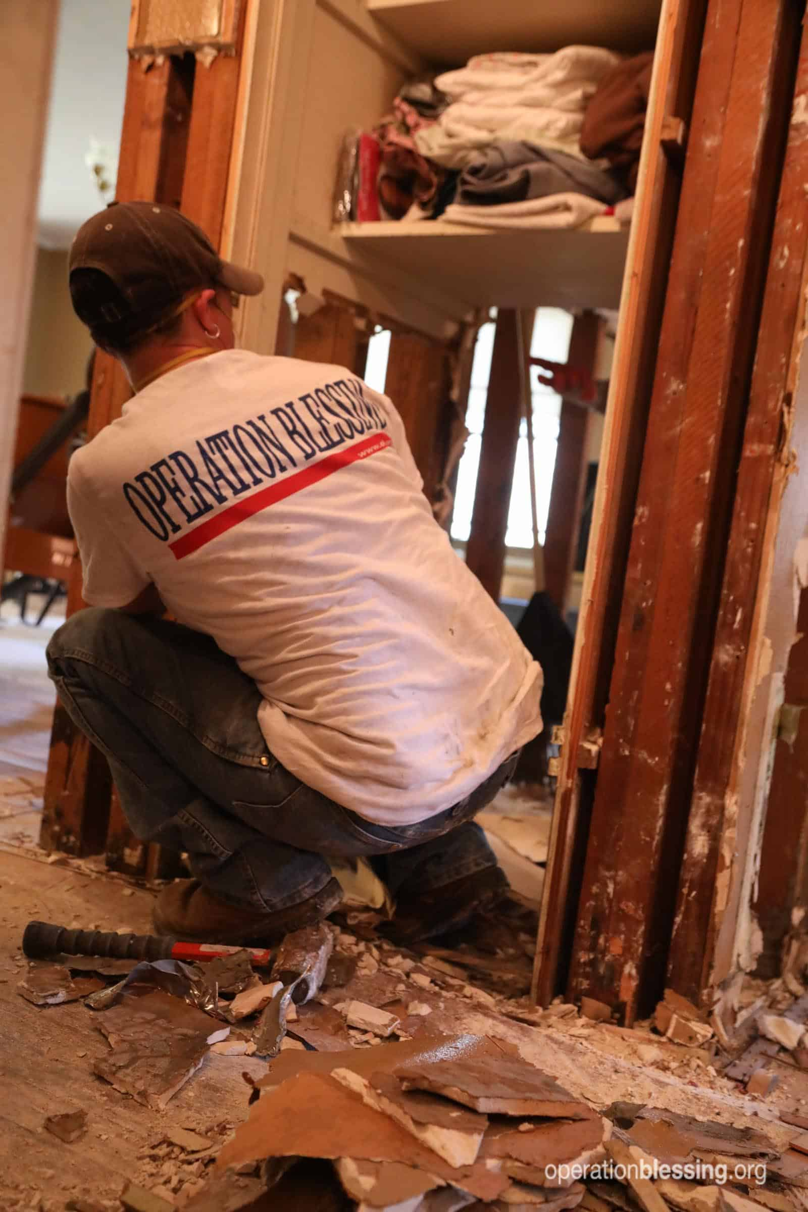 A volunteer works on gutting Donald's home.