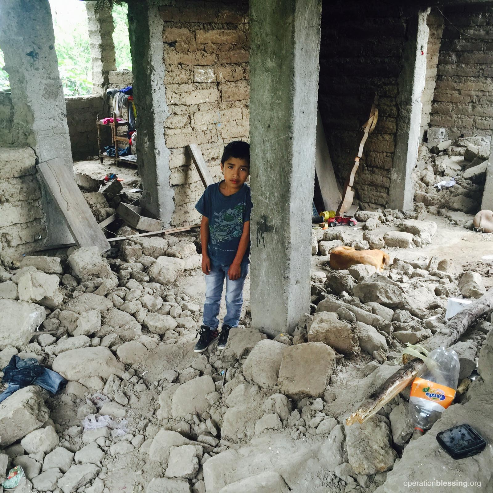 A sad young Guatemalan boy in his home destroyed by an earthquake.