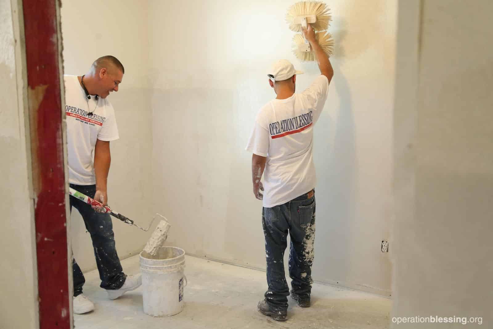 Volunteers repairing Jo and Herbert's walls.