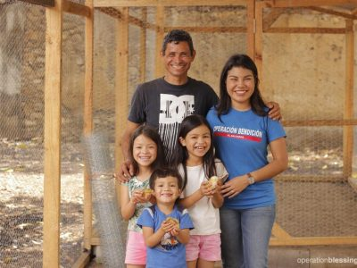 Widower Santos stand in front of his new chicken farm with his children and an OBI staff member. His dedication to his family is clear.