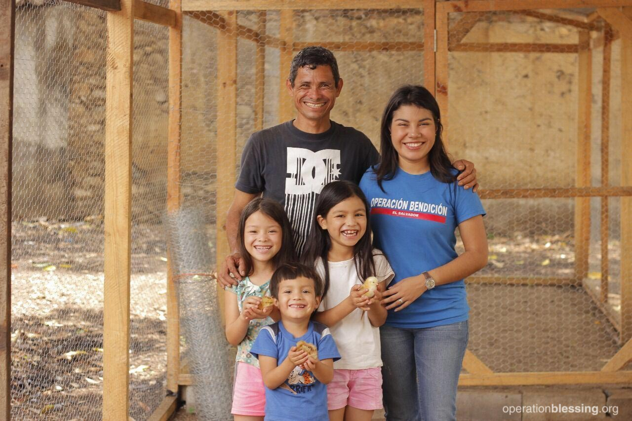 Widower Santos stands in front of his new chicken farm with his children and an OBI staff member. His dedication to his family is clear.
