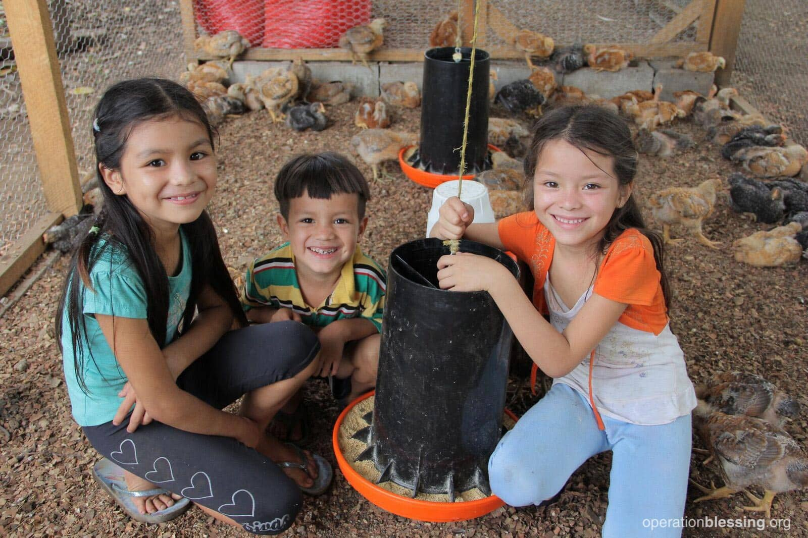 Santos's three happy children with the chickens in the coop.