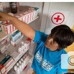 Frida reaches into her medical kit to provide health help for her community.