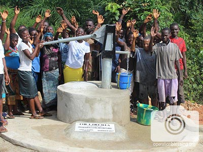 Villagers wave from a well that will help hundreds.