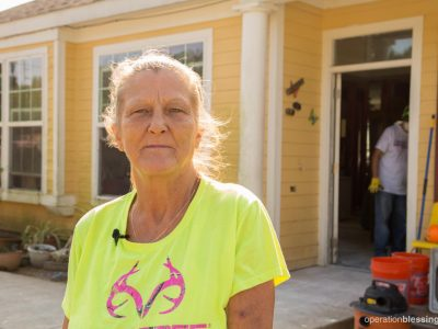 Brenda endured several tragedies in a short time. Here, she stands in front of her home which was devastated by Hurricane Harvey.