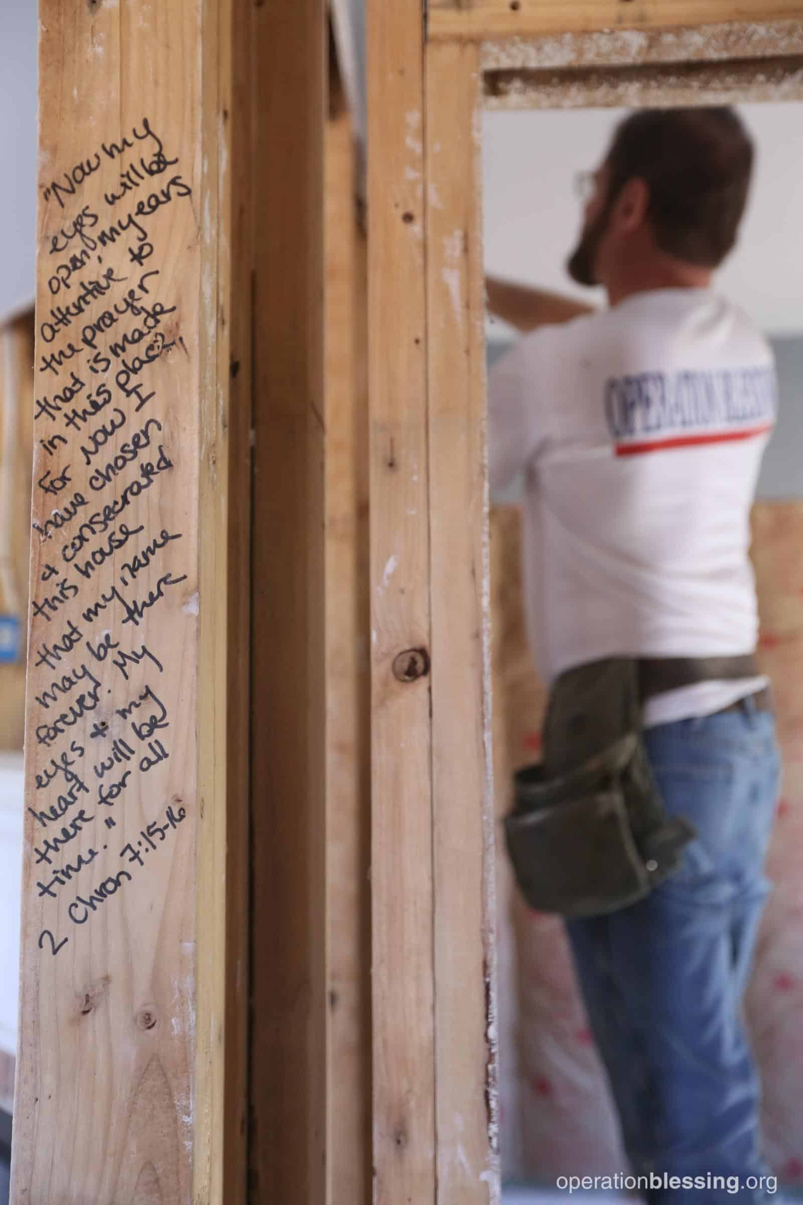 A Bible verse written on the beams as a volunteer works on Winderful's house.