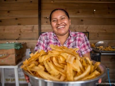 Elva happily holds her plantain chips, thankful for her newly transformed business.