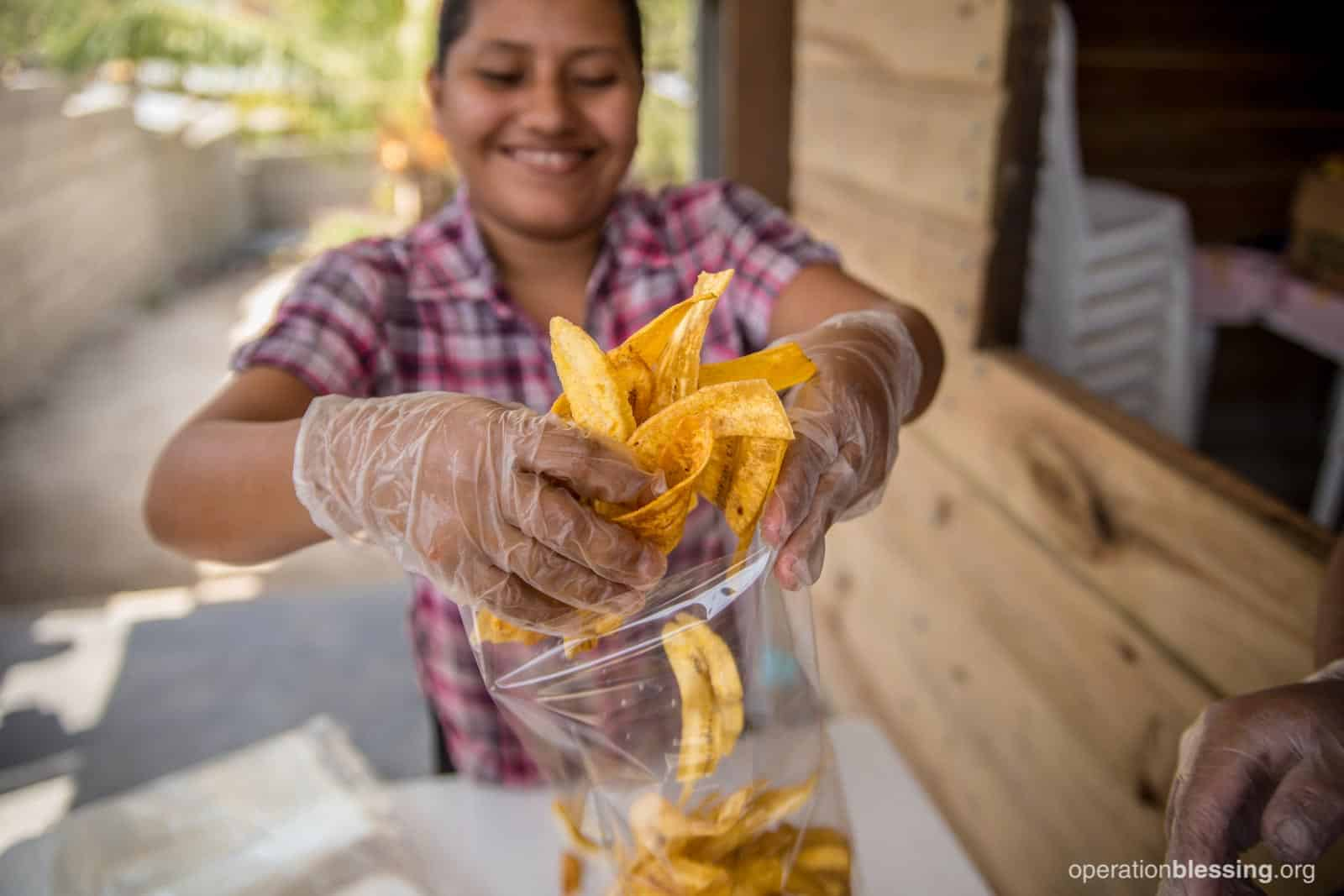 Elva packaging plantain chips to support her family.