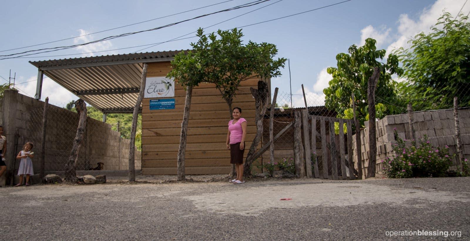 Elva stands in front of her new profitable kitchen.