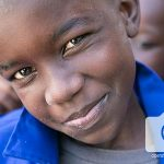A child in Senegal smiles at the camera.