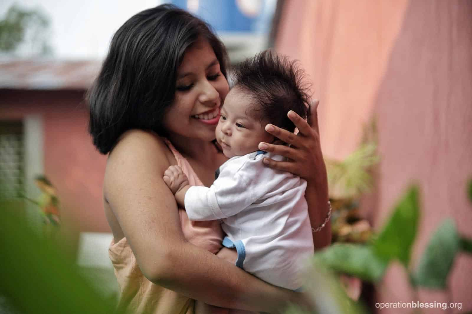 Iroska holds baby Thiago, the newest member of her family.
