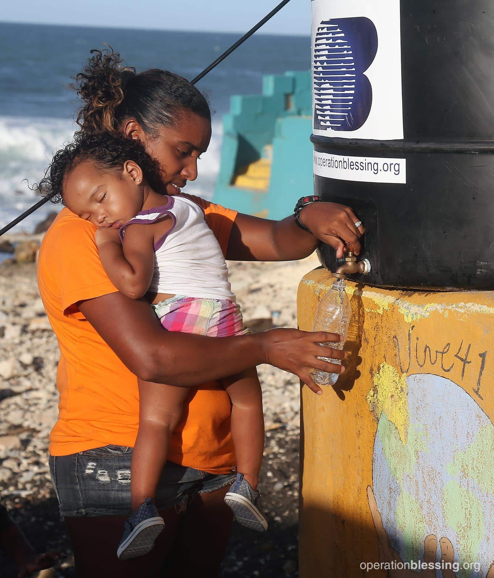 A mother and baby access safe water from OBI in Puerto Rico.