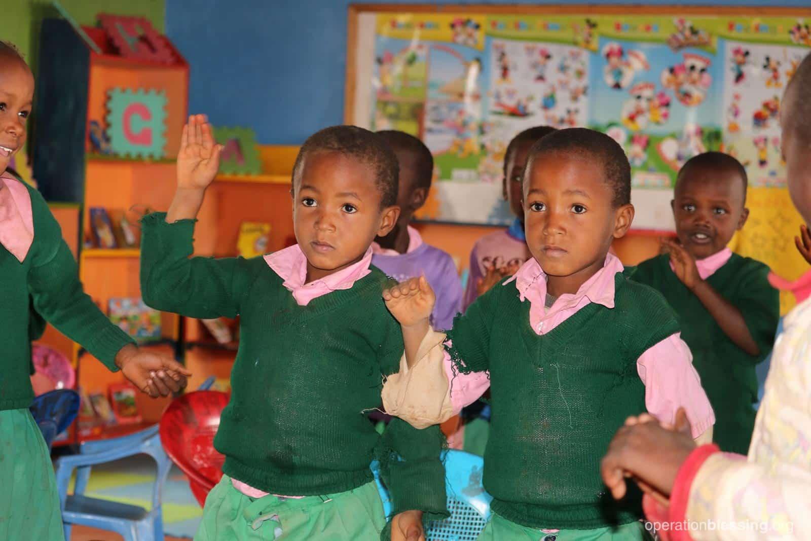 The twins in class in Kenya.