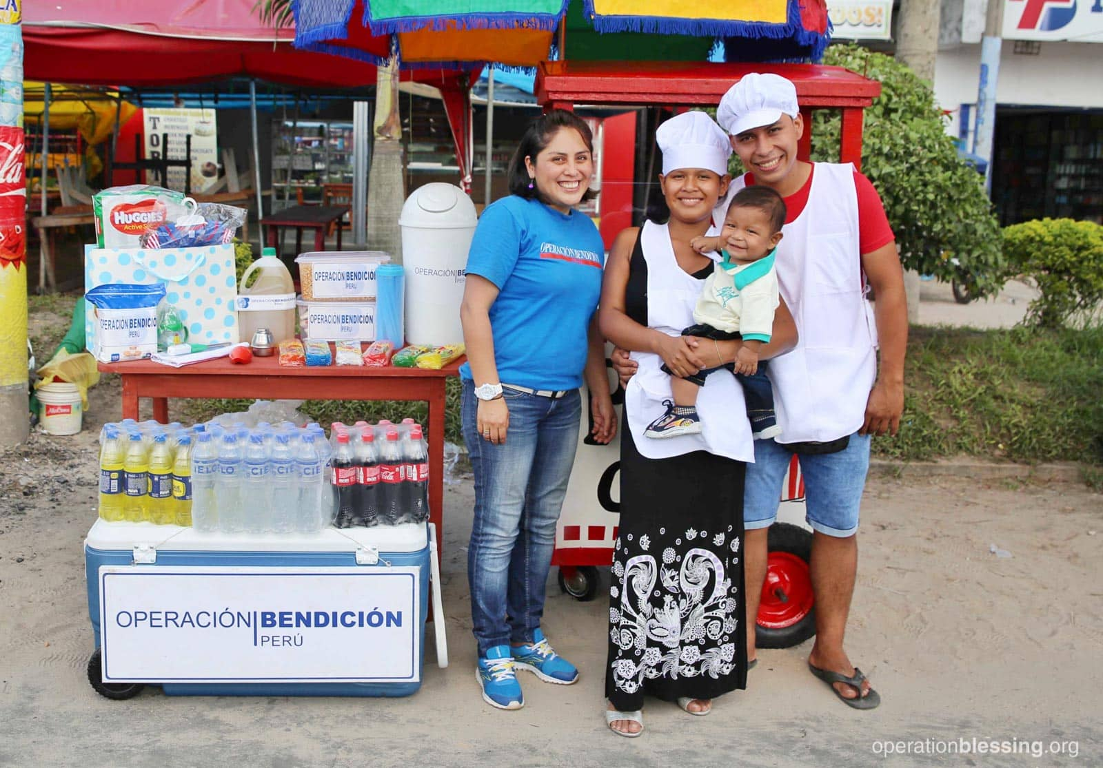 Young parents, Ines and Josue, stand in front of their improved popcorn business with their new son.