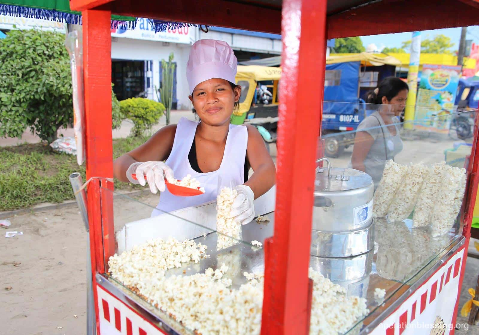 Ines serves popcorn from her refurbished popcorn cart, which will help her earn an income for her new baby.