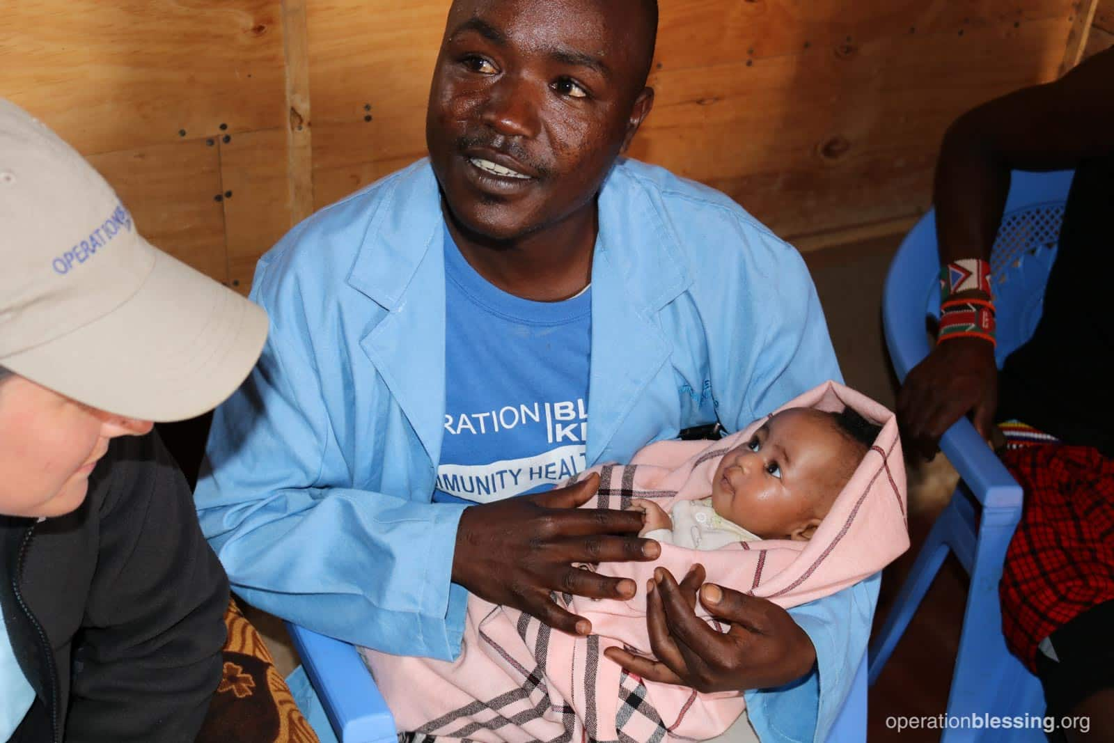 Samuel holds a healthy baby thanks to an OBI program encouraging mothers to seek safe childbirth.