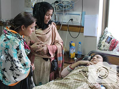 Two women stand at the bedside of one of the Pakistan church attack victims.