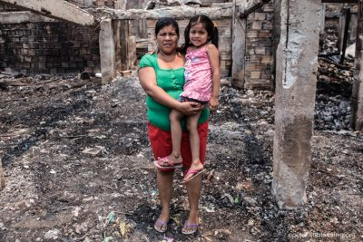 Ruth and her daughter in rubble after a single candle sparked the fire.