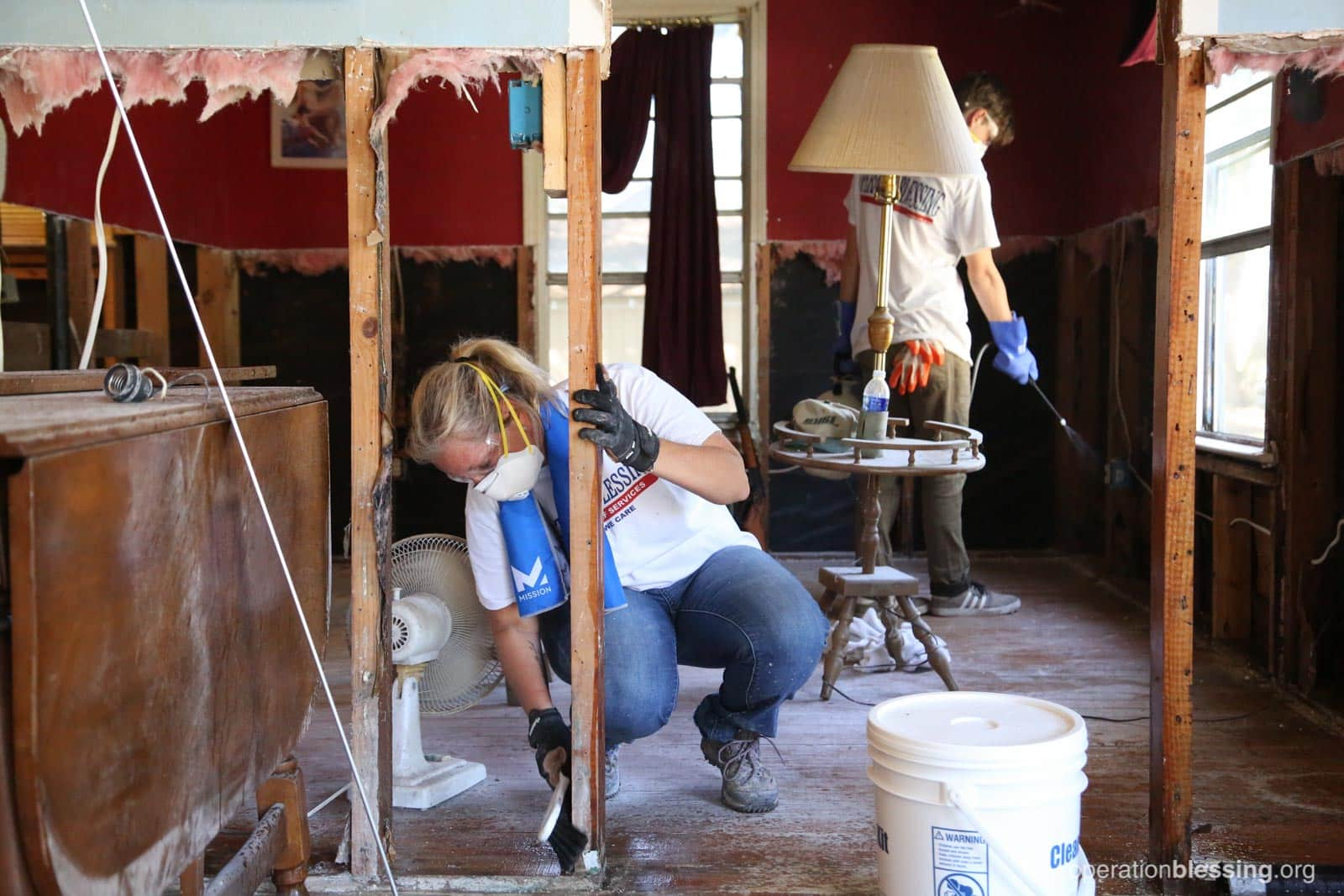 Volunteer Amy hard at work removing rotted and molding dry wall from the home of a Hurricane Harvey victim.