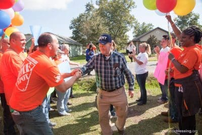 Allen approaches his new home makeover amidst balloons and cheering volunteers.