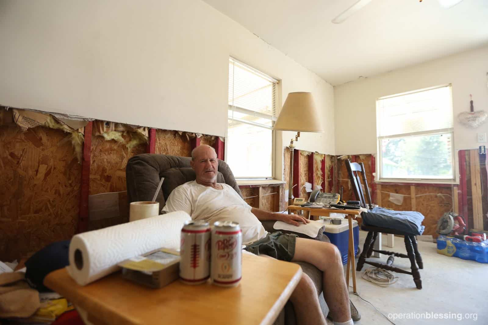 Allen sits in his stripped home on a single piece of furniture before the makeover.