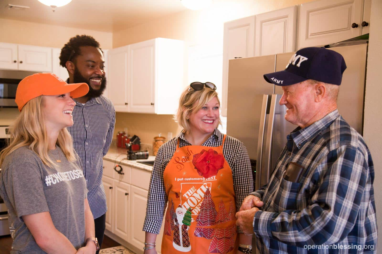Allen smiles in his newly made-over kitchen with some of the volunteers who remodeled his home.