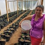 Bety smiles as she stands in front of the new crops grown in greenhouses built by OBI to support struggling families in her community.
