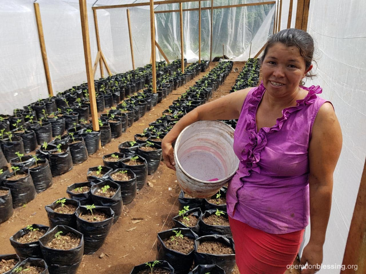 Bety smiles as she stands in front of the new crops grown in greenhouses  built by