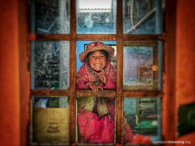 An adorable young girl peeks through a window in the Andes of Peru.