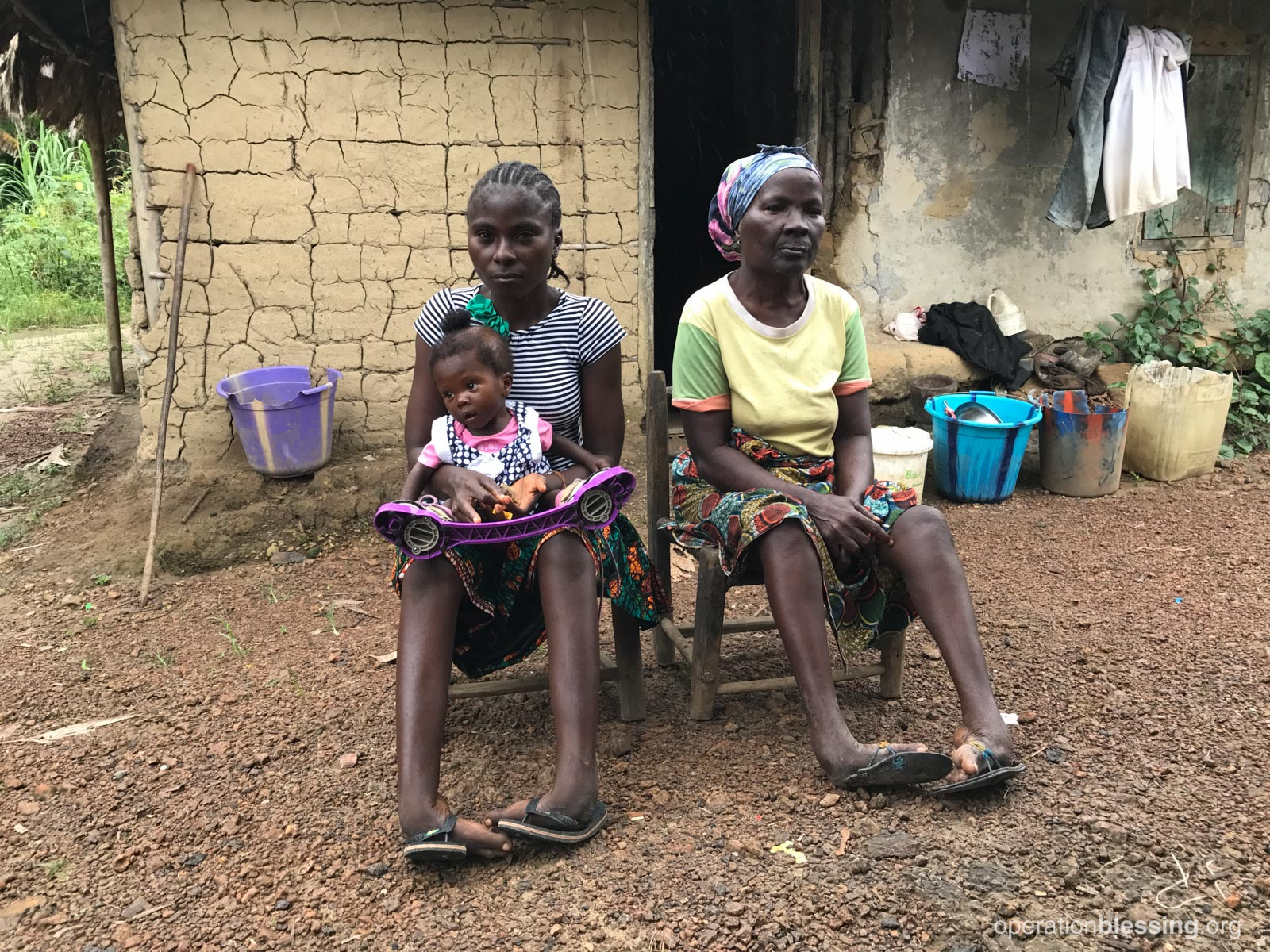 Miracles sits with her mother and grandmother. Her clubfoot treatment is in the bracing stage.