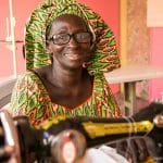 Ernestine sits at her new sewing machine, excited to recover her lost business.