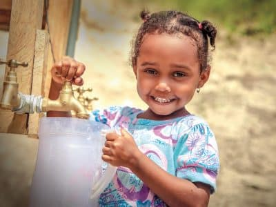 A young girl pouring safe water into a pitcher.
