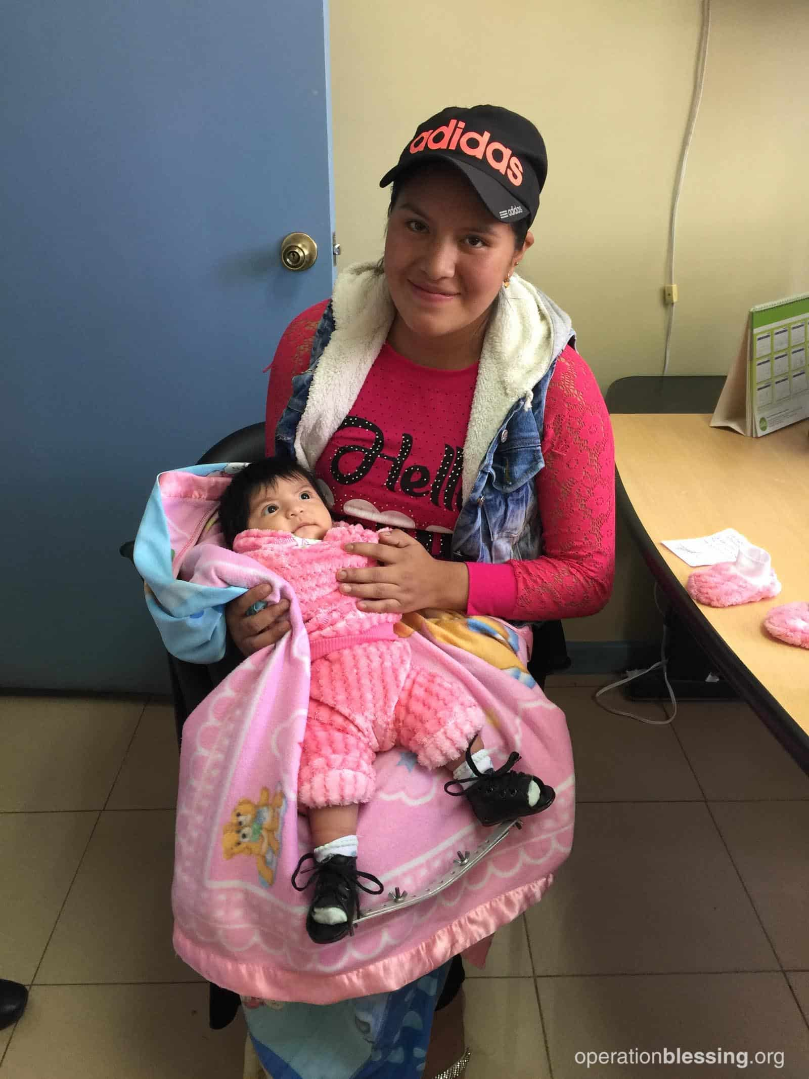 Belen holds little Yazmin with a smile on her face. One day, this little baby will take her first steps on corrected feet!