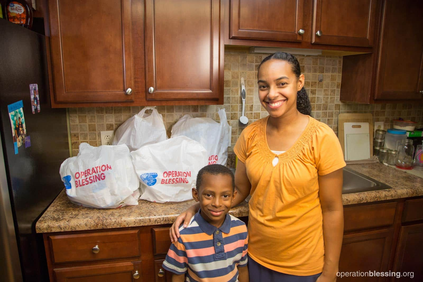 Erika stands with her gymnastics loving son in front of the groceries from House of Blessing.