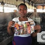 Beatrice stands in front of her stall in the Iron Market, holding a picture of it before the fire.
