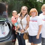 Kim stands with volunteers next to her trunk filled with groceries from House of Blessing.