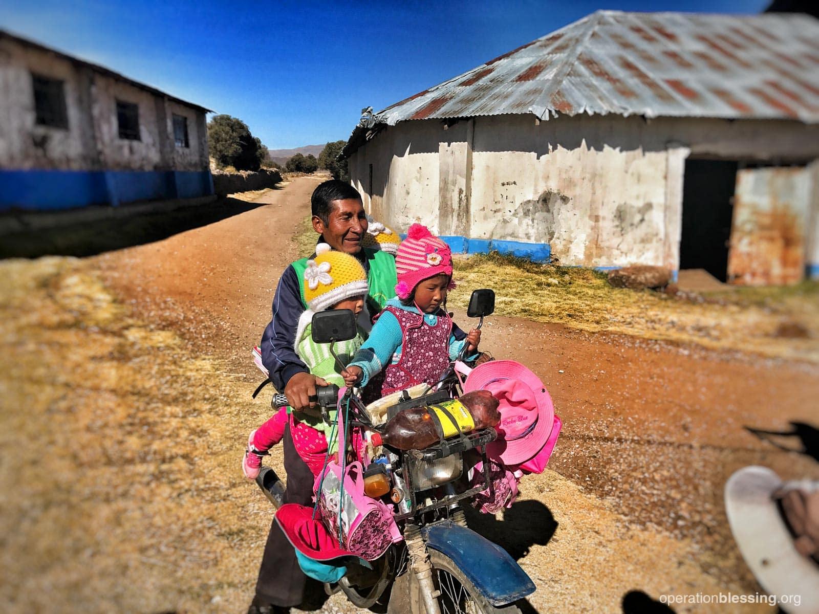Mr. Teófilo driving his preschool kids on his motorcycle.