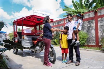 Roberth and his children gratefully accept his refurbished mototaxi from Operation Blessing.