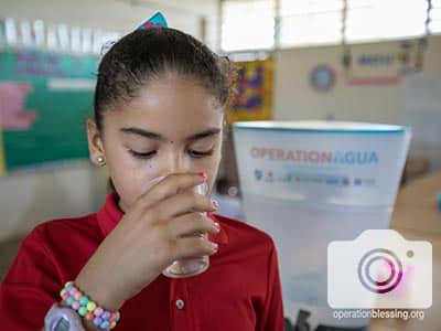 A child drinks from a Kohler Clarity unit delivered by Operation Agua.