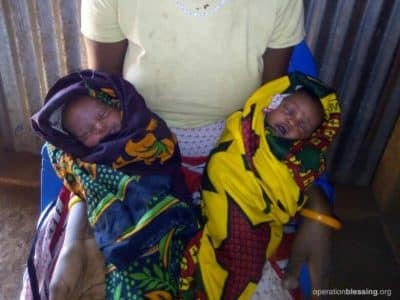 Naomi holds her surprise twins, Helen and Holly, safe after OBI provided for emergency prenatal care.