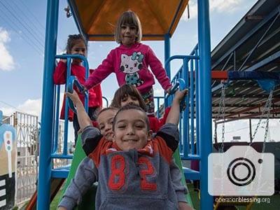 Children play at their West Bank Kindergarten on the new playground equipment.