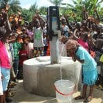 A young Liberian girl drinks deep from one of the new wells OBI built in her area.