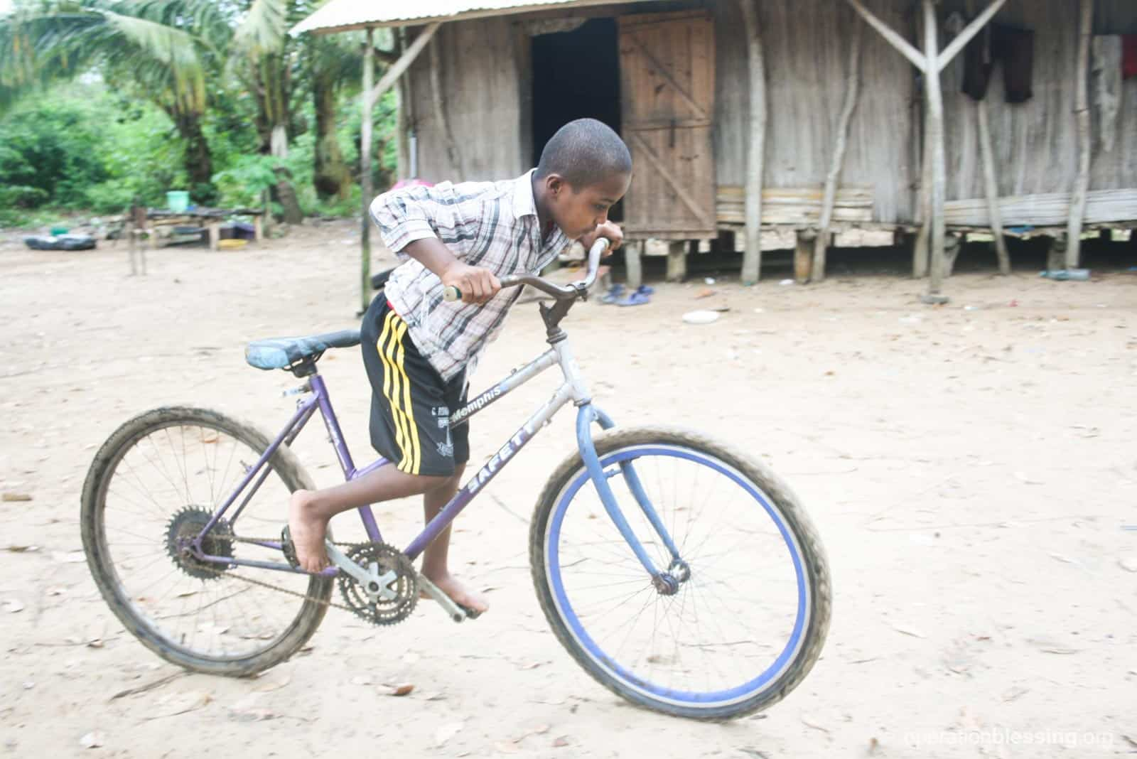 Juldo happily riding his bike through his village in Madagascar after suffering from clubfoot for a decade.