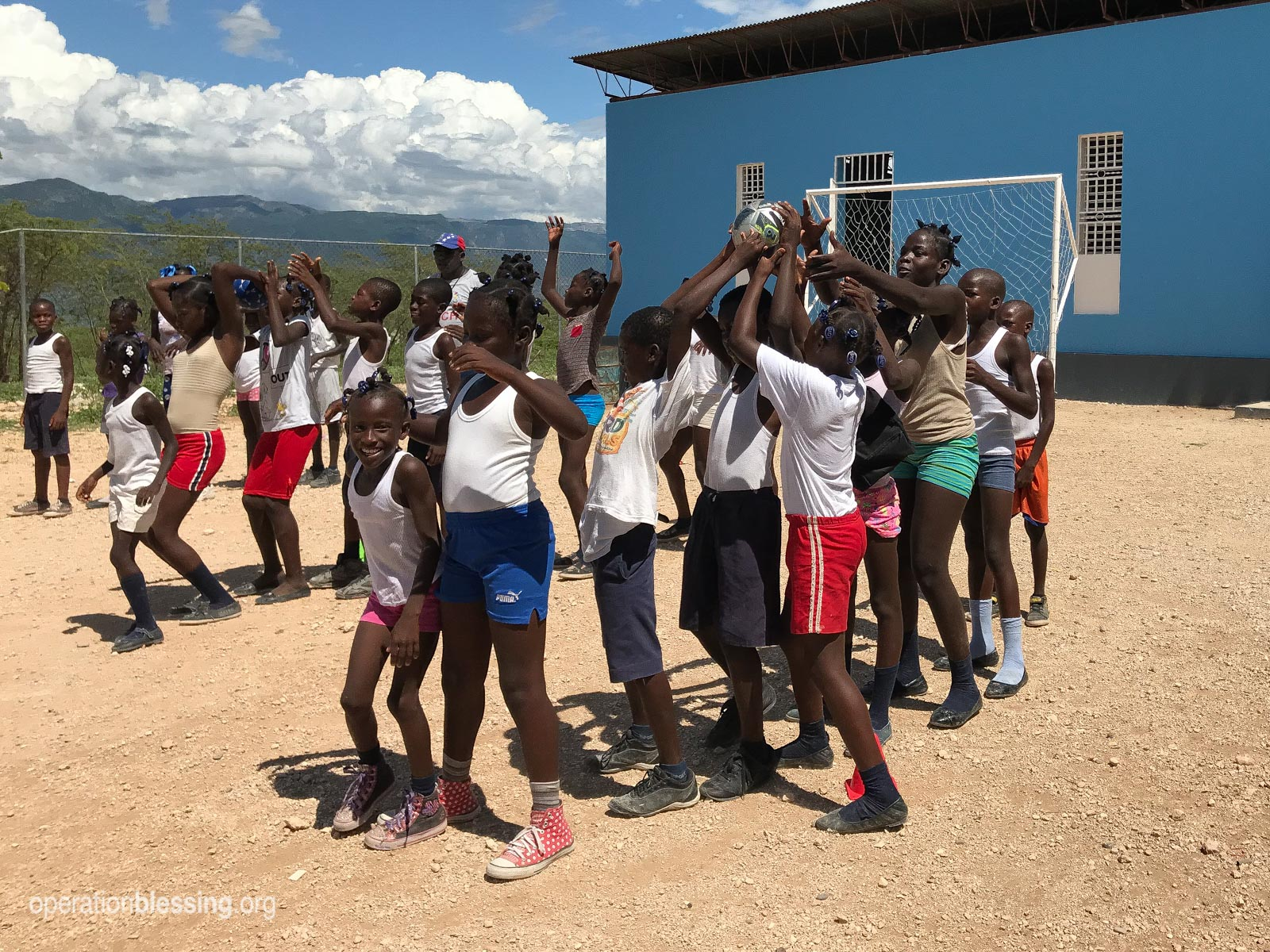 Kids in Haiti have fun during physical education class at OBI's ENLA school.