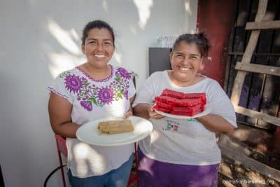 Bernarda and Francisca holding the candy and tamales they made in their new kitchen from Operation Blessing.