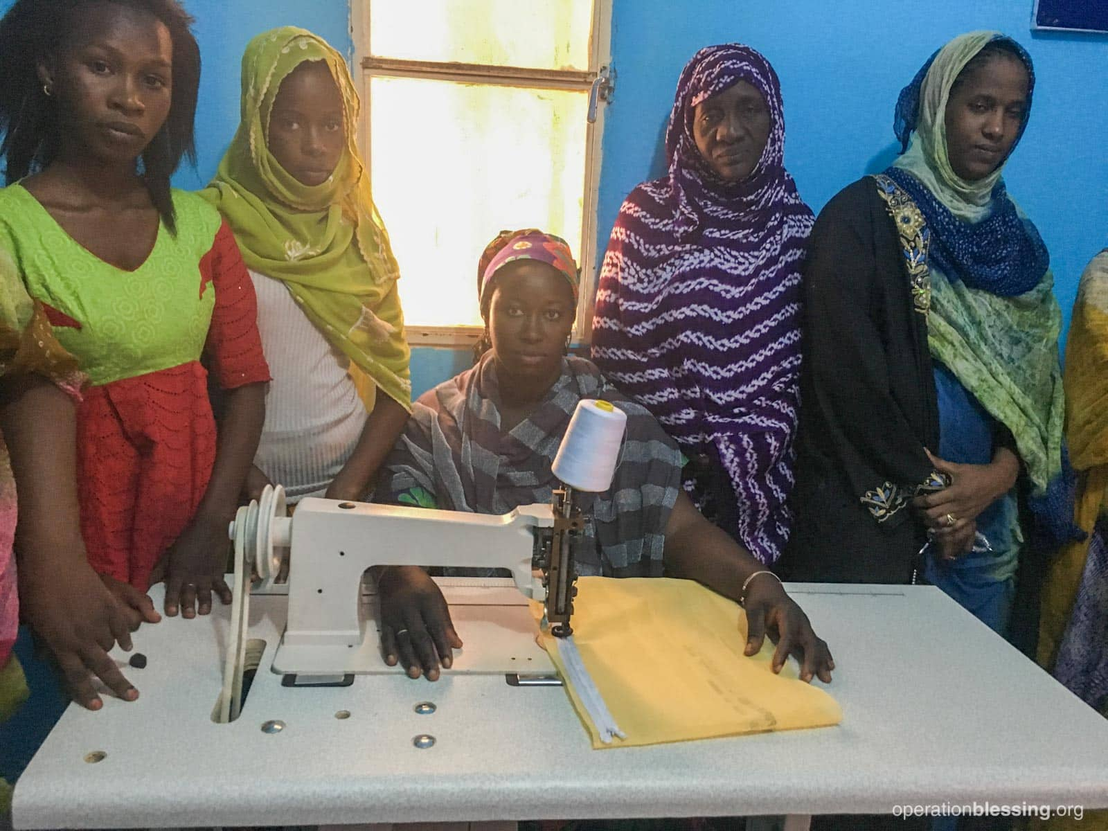 Women in Mauritania gather around the sewing machine for their lesson.