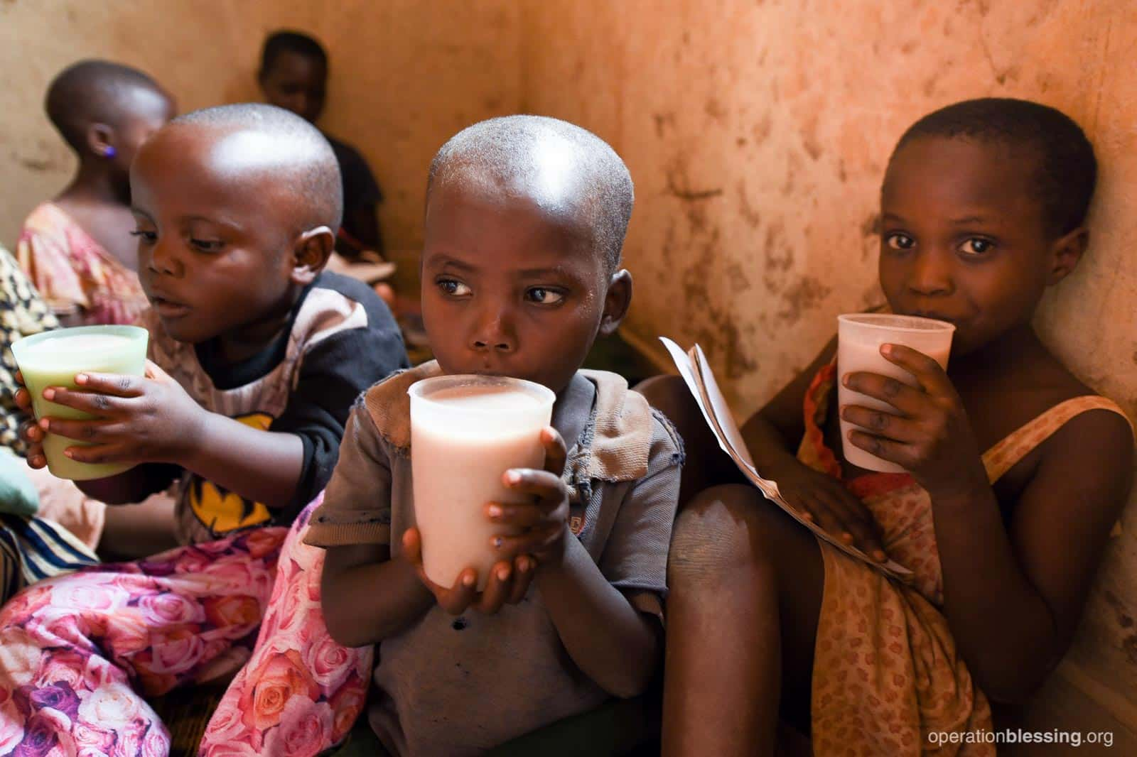 The twins drinking big cups of milk.